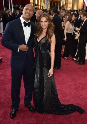 Actor Dwayne 'The Rock' Johnson (L) and Lauren Hashian pose on the red carpet for the 87th Oscars on February 22, 2015 in Hollywood, California. AFP PHOTO/ MLADEN ANTONOV        (Photo credit should read MLADEN ANTONOV/AFP/Getty Images)